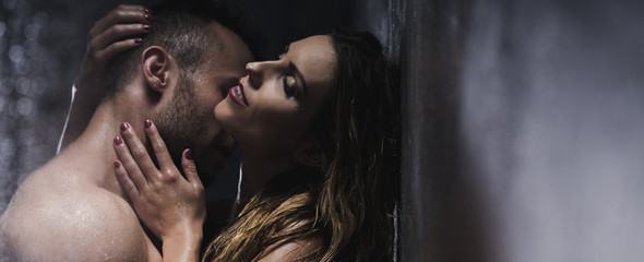 Man embracing his sexy girlfriend in the shower