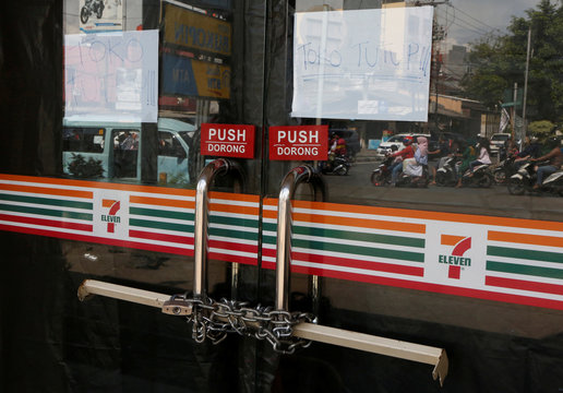 Chains are used to lock the front door of a 7-Eleven convenience store in Jakarta