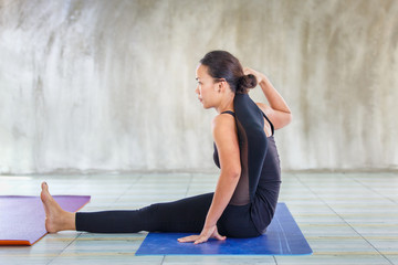 Asian trainee strong woman practicing difficult yoga pose in a concrete background, Sport healthy concept