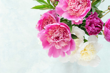 Peonies. Beautiful bouquet of pink white and purple peonies in vase on bright background. Closeup shot selective focus. Wedding bouquet, mothers day gift, women's day gift