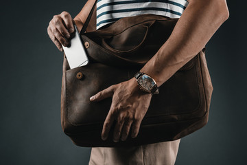 cropped view of stylish man with watch putting smartphone into leather bag, isolated on grey