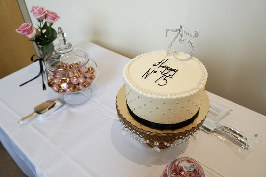Birthday cake display with tablecloth foiled candy and roses in a vase or anniversary celebration classy beaded round cake
