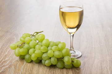 Glass of white wine and bunch of grape on table