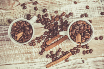 Fragrant coffee beans in small cups and cinnamon sticks