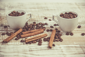 A stick of cinnamon and grains of coffee with a cup on a vintage table