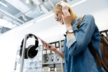 Low angle shot of female customer checking template headphones