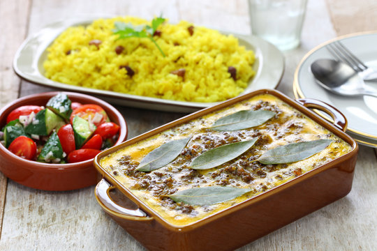 bobotie and yellow rice, south african cuisine. bobotie is a curry flavored meatloaf with baked egg on top.