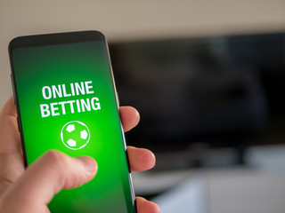 Online sports betting app on smart phone. Man holdning device.