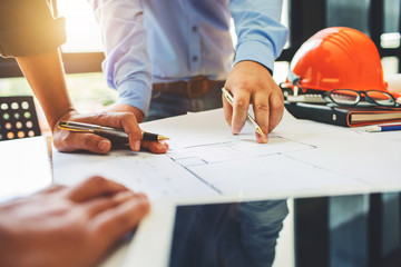 Architecture engineering teamwork meeting at workplace to plan drawing a new blueprint busy working hard for apartment building small business of their customer service. Wall mural