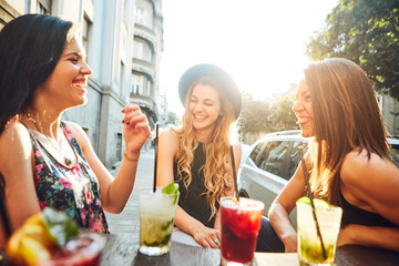 Three young woman at cafe drinking and having fun