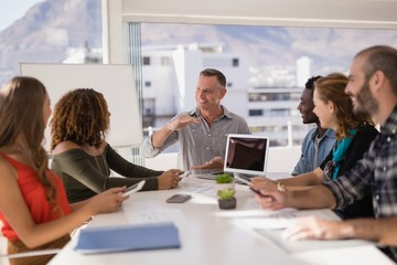 Executive having discussion in conference room