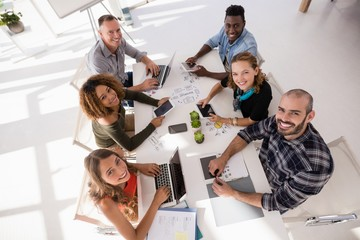 Portrait of happy colleagues sitting at conference table