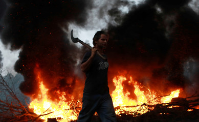 MTST walks near a burning barricade on BR-290 highway during a protest against President Temer's proposal to reform Brazil's social security system, during the general strike in Eldorado do Sul