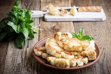 Roasted organic cauliflower steak on wooden board
