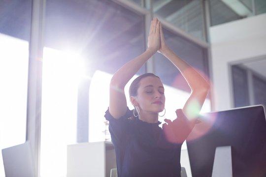 Female executive doing yoga
