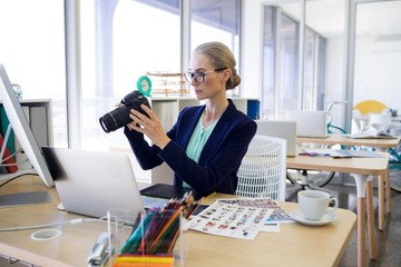 Female executive reviewing captured photograph at her desk