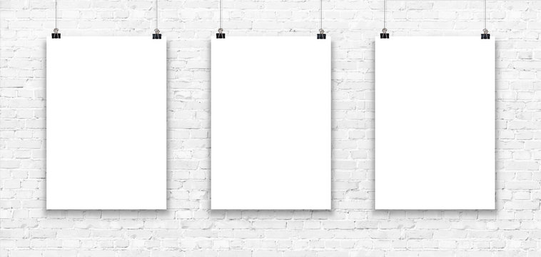 Three blank paper poster mockup on a white brick wall.