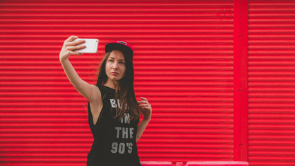 Young pretty hipster style sexy girl having fun outdoors, making a selfie with her smarthpone, red wall background urban style