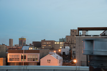 Lovely shot of city apartment buildings from a rooftop in the evening, just after sunset.