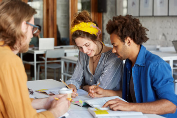 Group of three interracial students meeting together in classroom working with books writing something with pencils preparing for final test together having smiles on their faces. Education concept