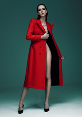 Fashion model with wet hair wearing red long coat