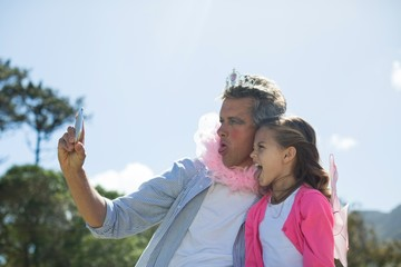 Smiling father and daughter in fairy costume taking selfie on mobile