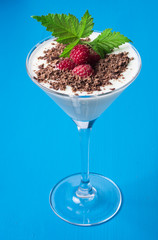 Raspberries, chocolate and mint with yoghurt, milk, cottage cheese in a martini glass. Delicious and bright dessert.