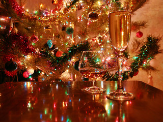 Festively decorated with toys and lights Christmas tree and glasses with alcohol on the table