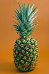 whole ripe pineapple on orange background, isolated