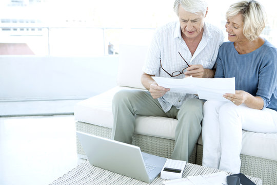 Retired senior couple doing home finance with paperwork, laptop and calculator