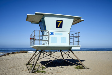 Beach lifeguard tower on the California coastline against blue skies