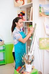 beautiful young girl draws a picture paints on art lesson
