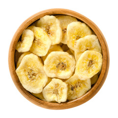 Dried banana chips in wooden bowl. Yellow deep fried slices of bananas, covered with sugar or honey. Snack with sweet taste. Isolated macro food photo close up from above on white background.