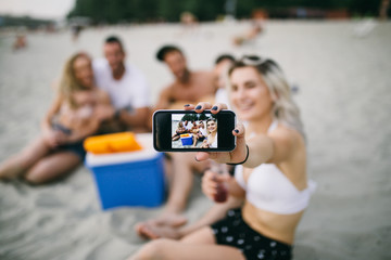 Group of attractive young people enjoying holiday beach fun and making selfie photo.