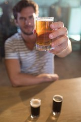 Portraut of man holding beer glass at bar counter