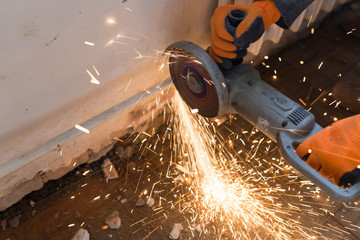 Worker cuts a metal pipe at a construction site