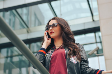 Beautiful young brunette business woman standing on the street near a shopping center and talking on a mobile phone