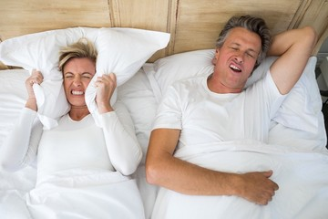 Annoyed woman covering ears with pillow while man snoring on bed