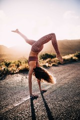 Young caucasian woman doing yoga on road