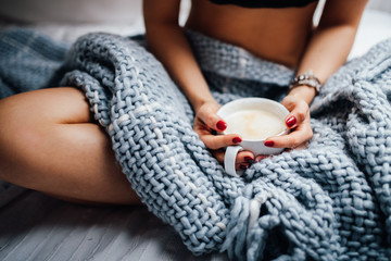 Close-up of women holding fresh cup of coffee in bed