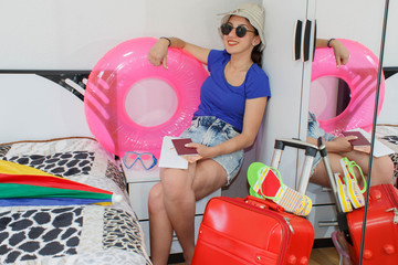 Happy young woman in colorful summer outfit sitting near the red staffed suitcase, smiling