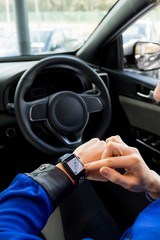 Cropped image of woman using smart watch in car