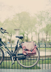 Vintage bicycle with a messenger bag in a fence  in Paris