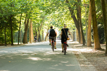Man & woman biking in a sunny Vondelpark.