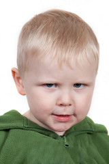 Toddler frowns angrily. Cranky face.