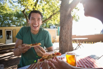 Happy man looking at friend while having pizza
