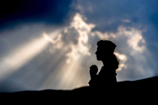 Silhouette young woman prayer.