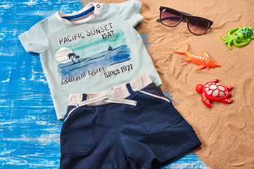 Baby Child summer stuff to the beach on a blue wooden background with sand. Top view.