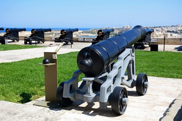 Cannons in Upper Barrakka Gardens with views across the harbour towards Vittoriosa, Valletta.