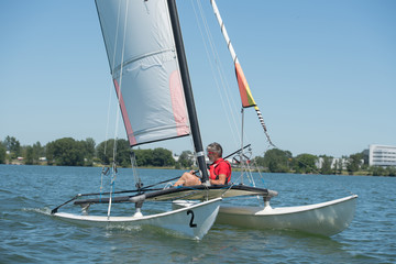 catamaran sailing boat and man in a sunny day